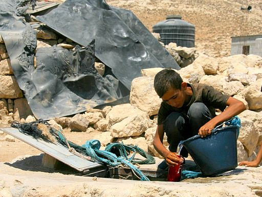 Boy draws water from cistern in the village of Khirbet Jenbah, South Hebron Hills, which is not hooked up to water grid. By Sharon Azran, B'Tselem.